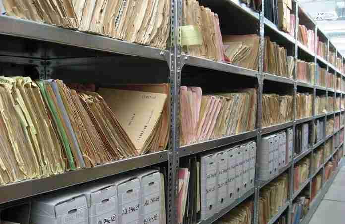 Un archivio documentale con faldoni e carte usurate