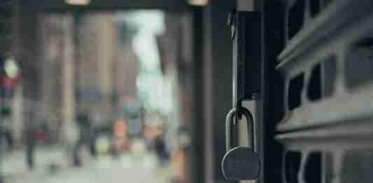 La saracinesca di un negozio chiusa da un lucchetto